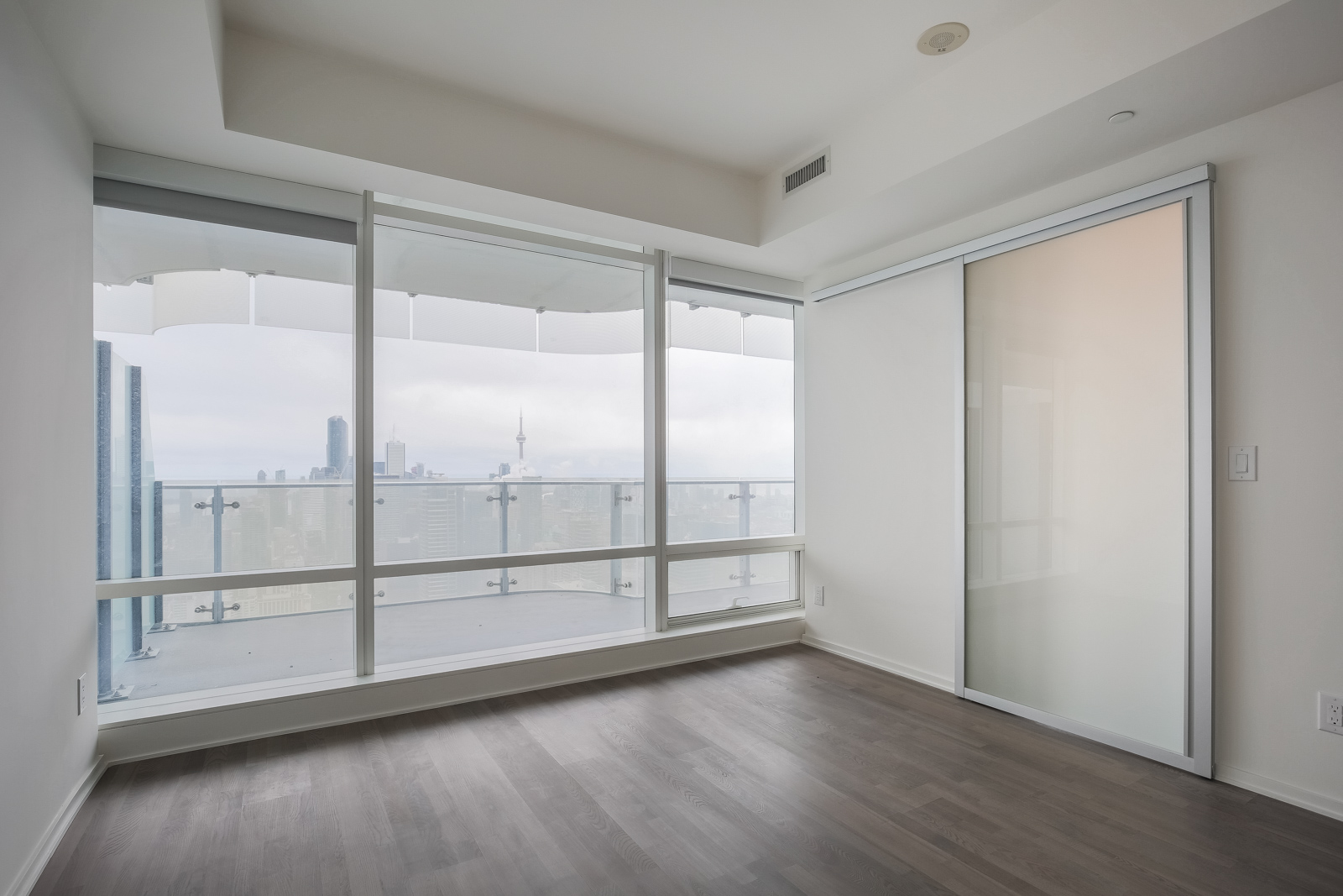Picture showing large glass windows and view of Toronto from bedroom