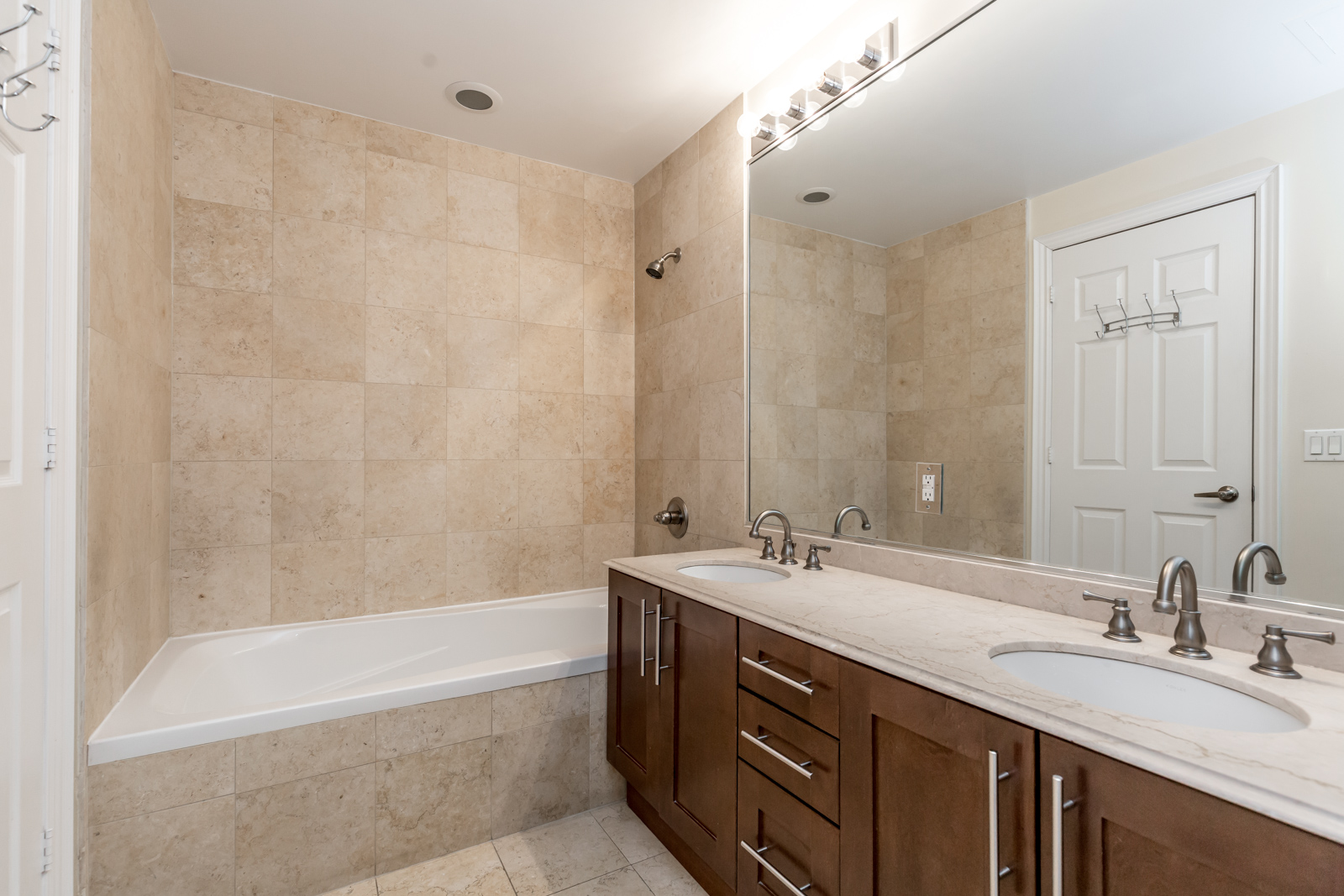 Photo of master bathroom with large mirror, 2 sinks, and bathtub.