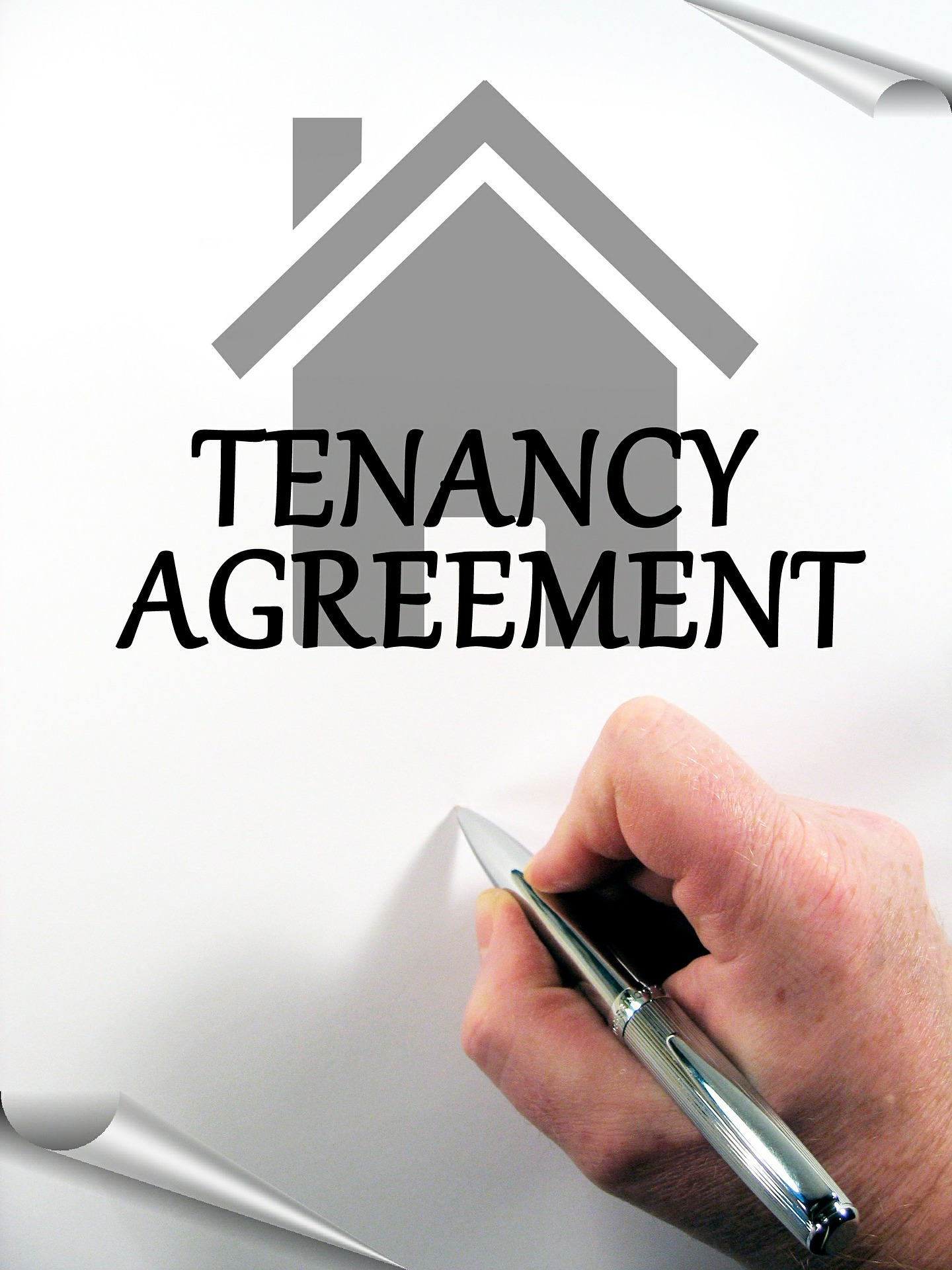 "Photo of hand holding pen over a piece of paper saying ""Tenancy Agreement."" There's a house; best real estate agents in Toronto."