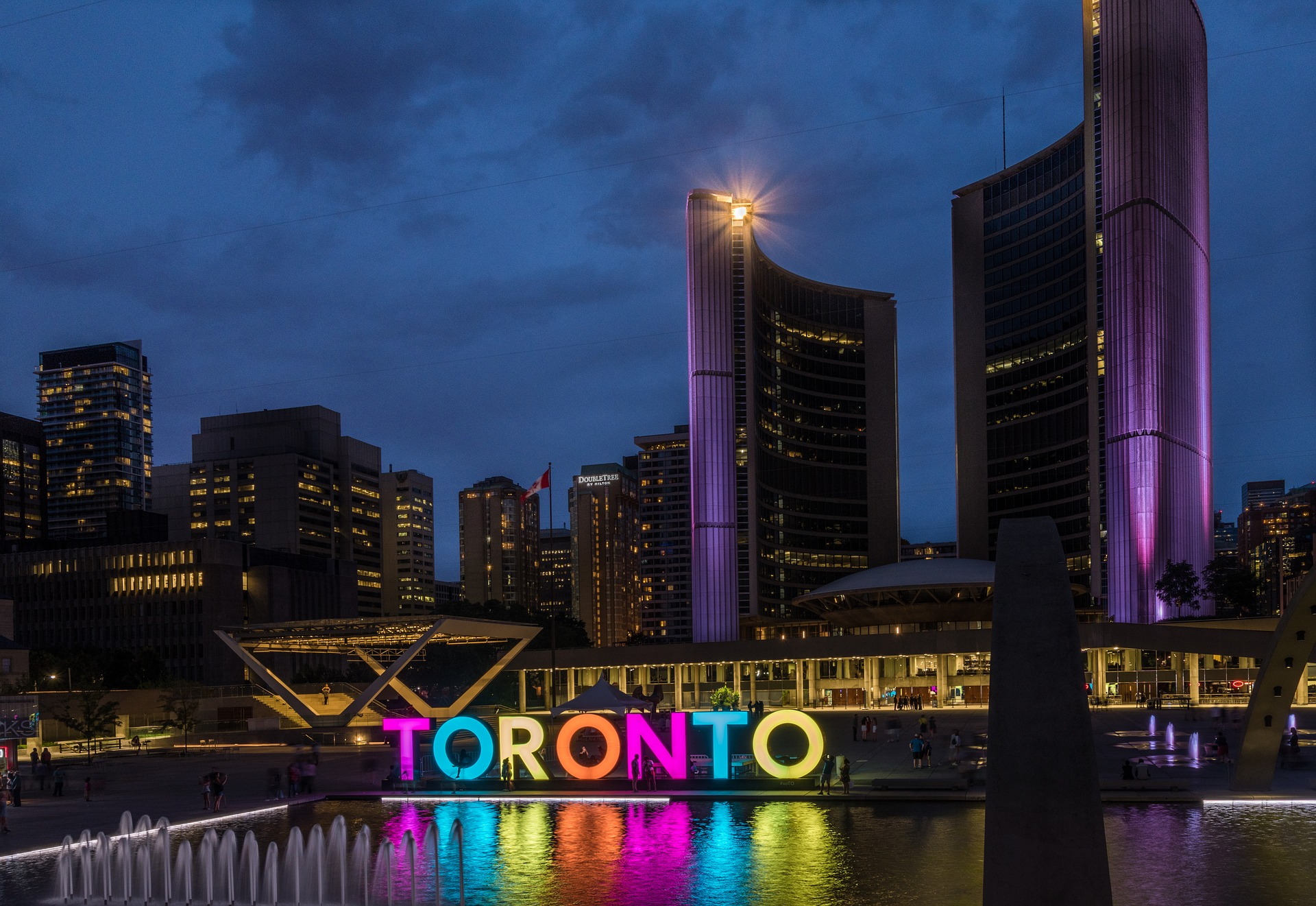 Photo of Toronto City Hall at night. The Toronto sign is lit up and Toronto real estate agent.