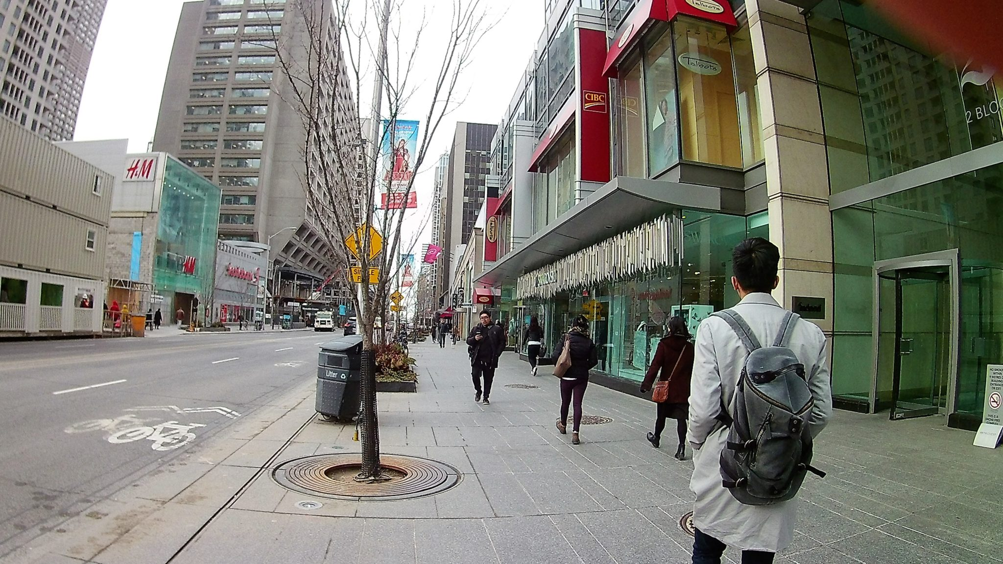 Photo of Bloor street showing people, banks, shops, and buildings.