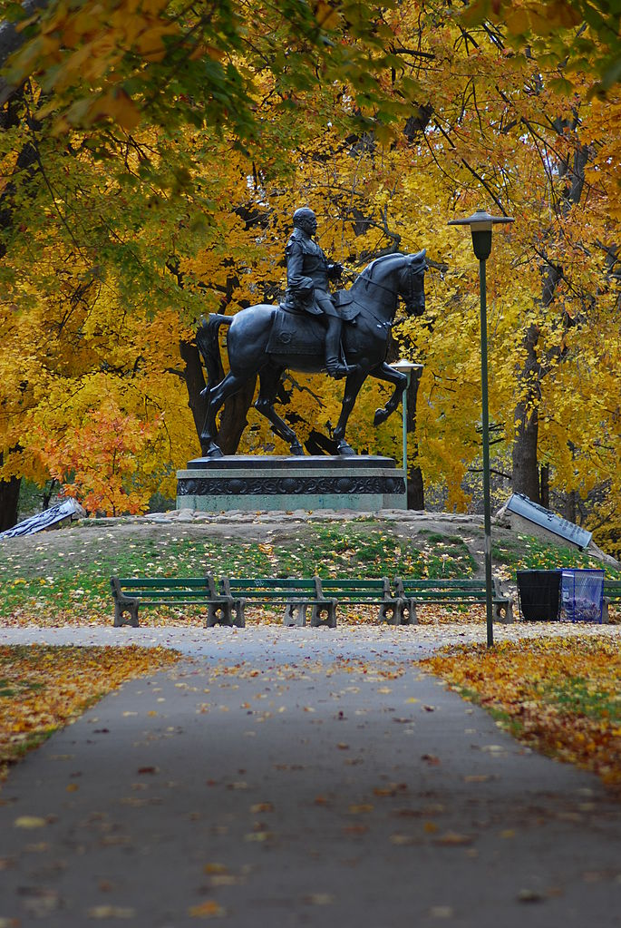 Photo of Queen's Park, trees, and statue.