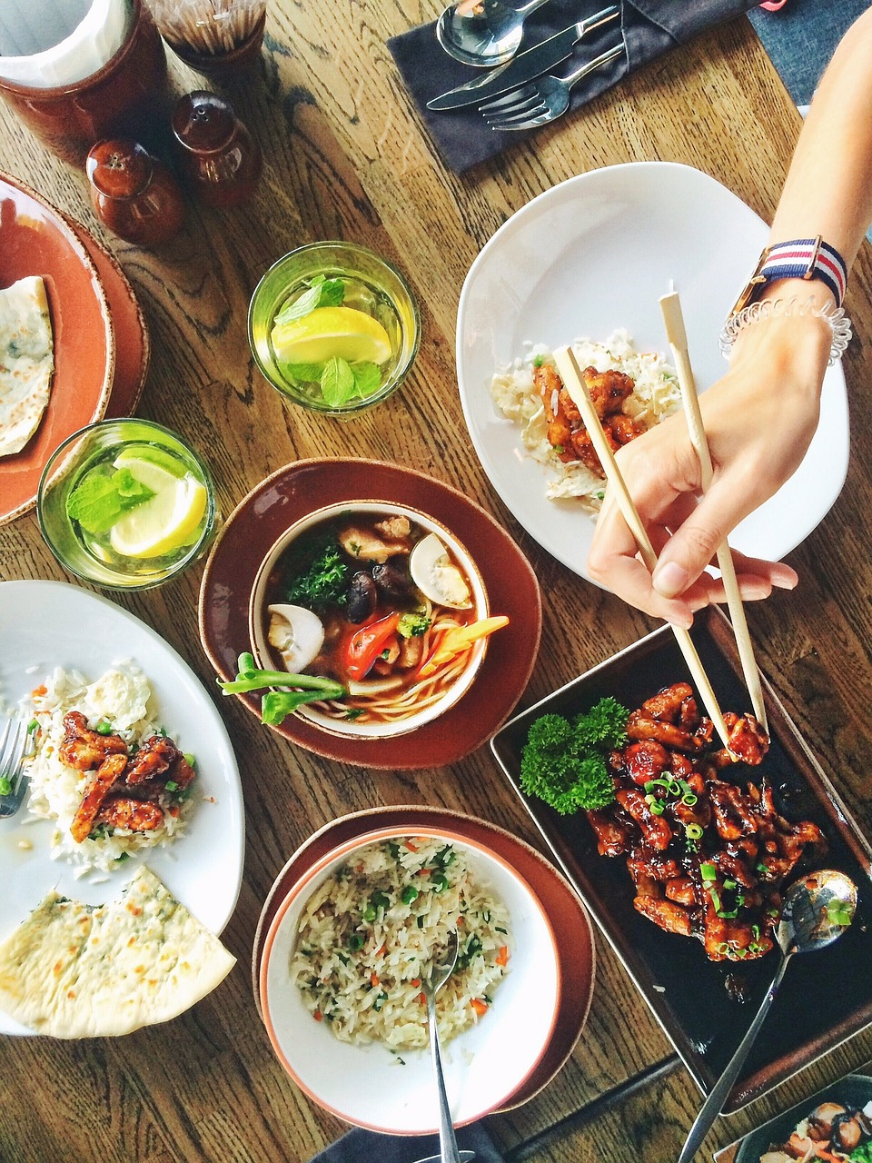 Photo of table with food and hand holding chopsticks.