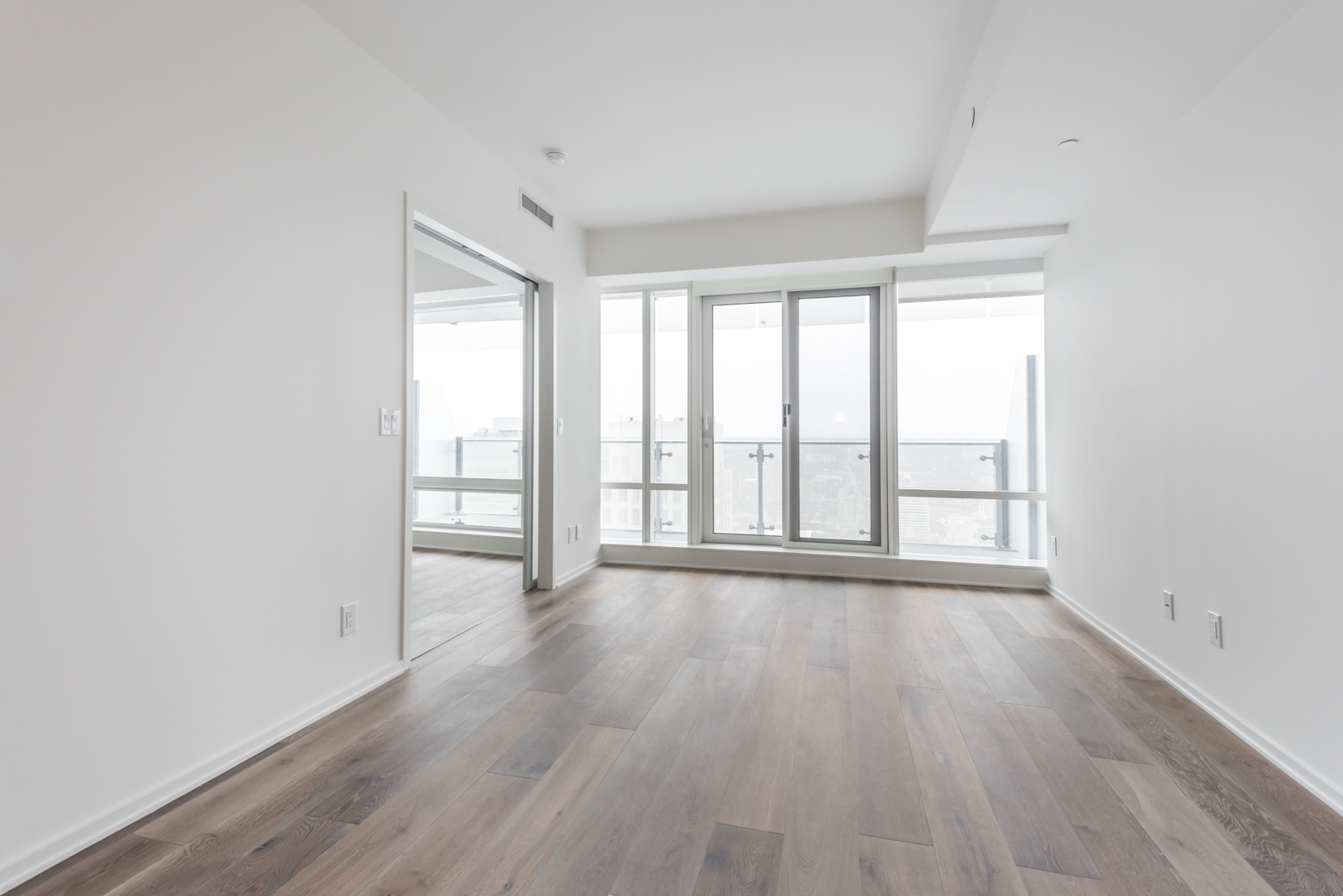 Photo showing large windows, screens, white walls, and so many other highlights of 1 Bloor. It seems like, maybe, probably, almost most of all, most noteworthy, and being a Toronto real-estate agent is especially relevant.