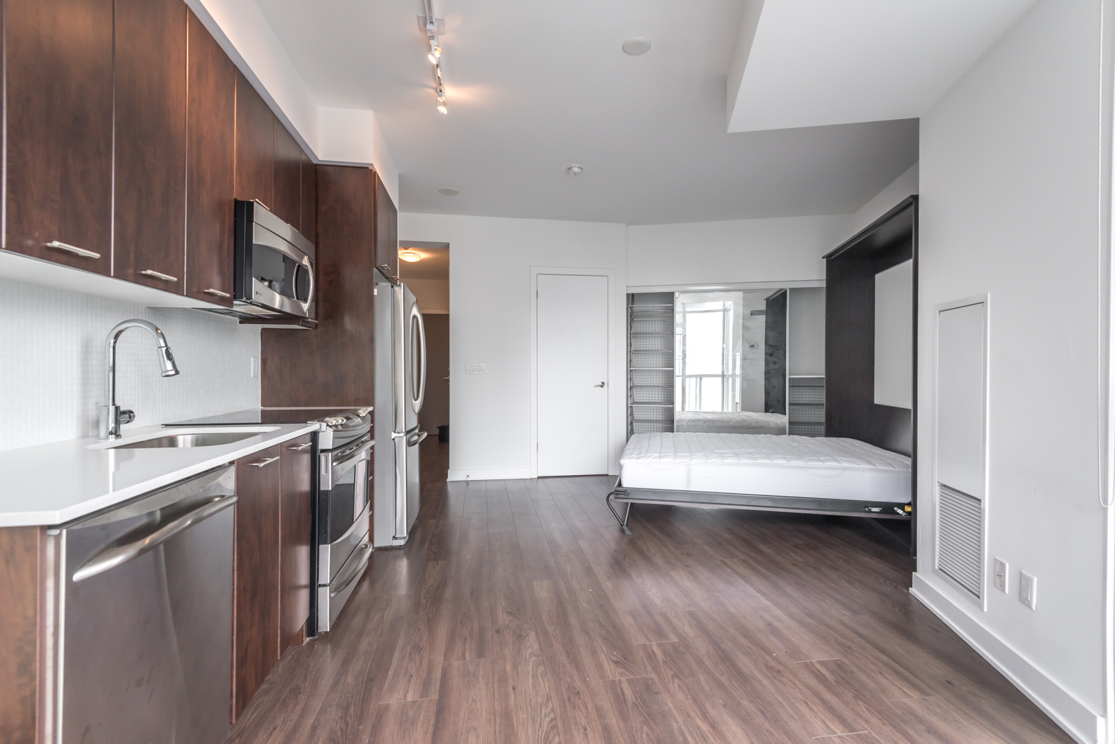 Image of condo showing kitchen, open bed, and also the brown floors.