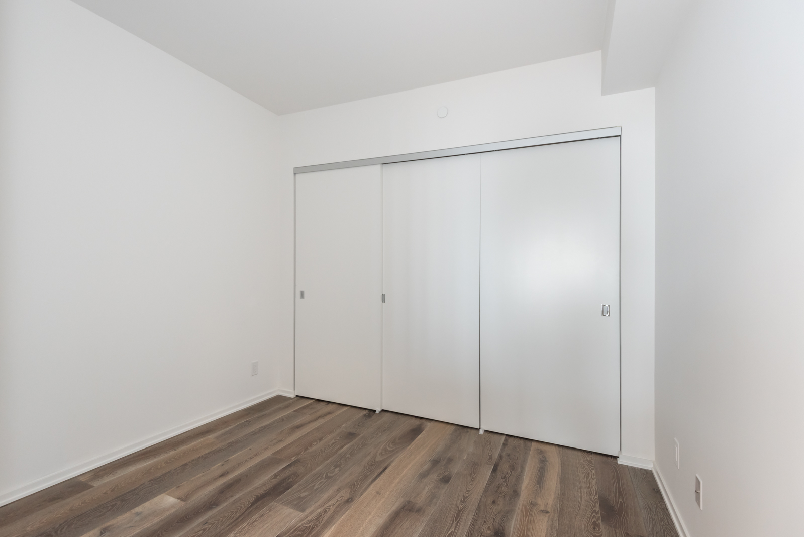 Photo of 2nd bedroom showing large closet doors.
