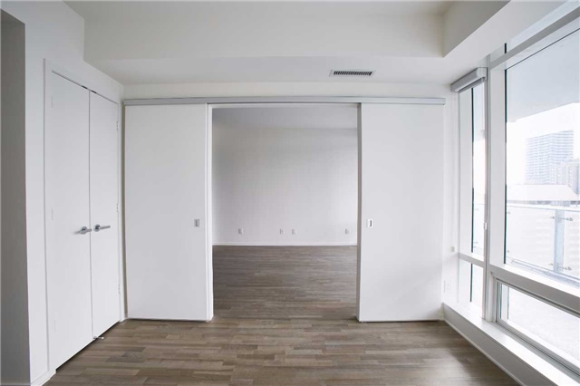 Rear view of 1 Bloor Unit 3109 master bedroom with doors open. Much as the rest of the condo, the doors are white while the hardwood floors are brown.