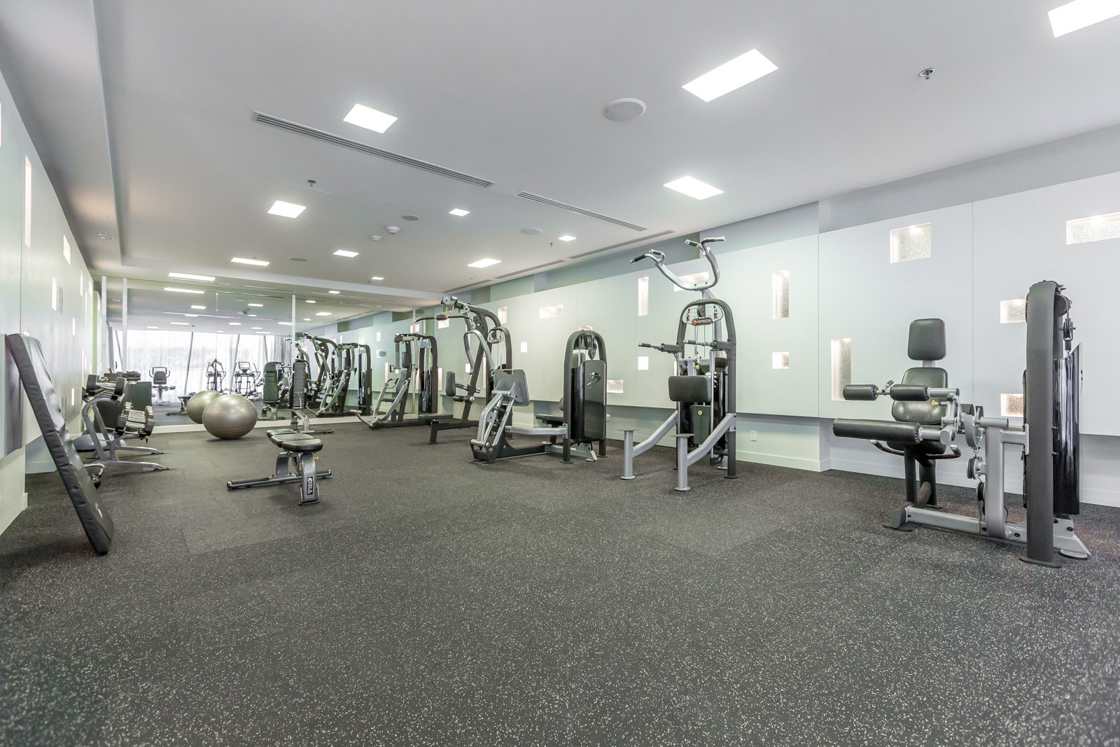 Photo of condo's fitness centre. Picture shows so many pieces of equipment. The space is rather large.