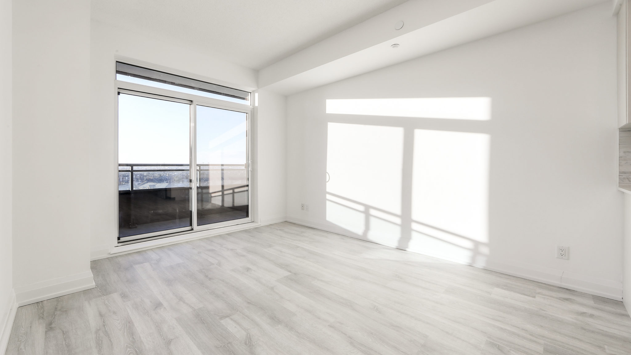 Picture of living room and glass doors. We also see so much sunlight pouring into the room.