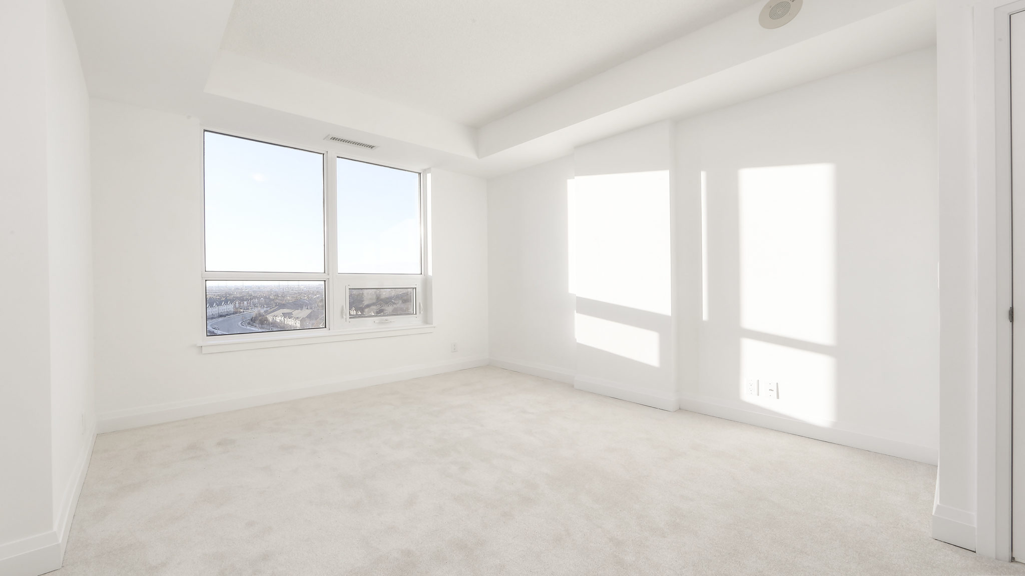 Bedroom photo showing windows and sunlight. The white carpet almost blends into the walls.