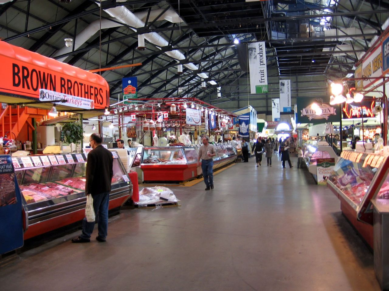 Stalls and people shopping at market.