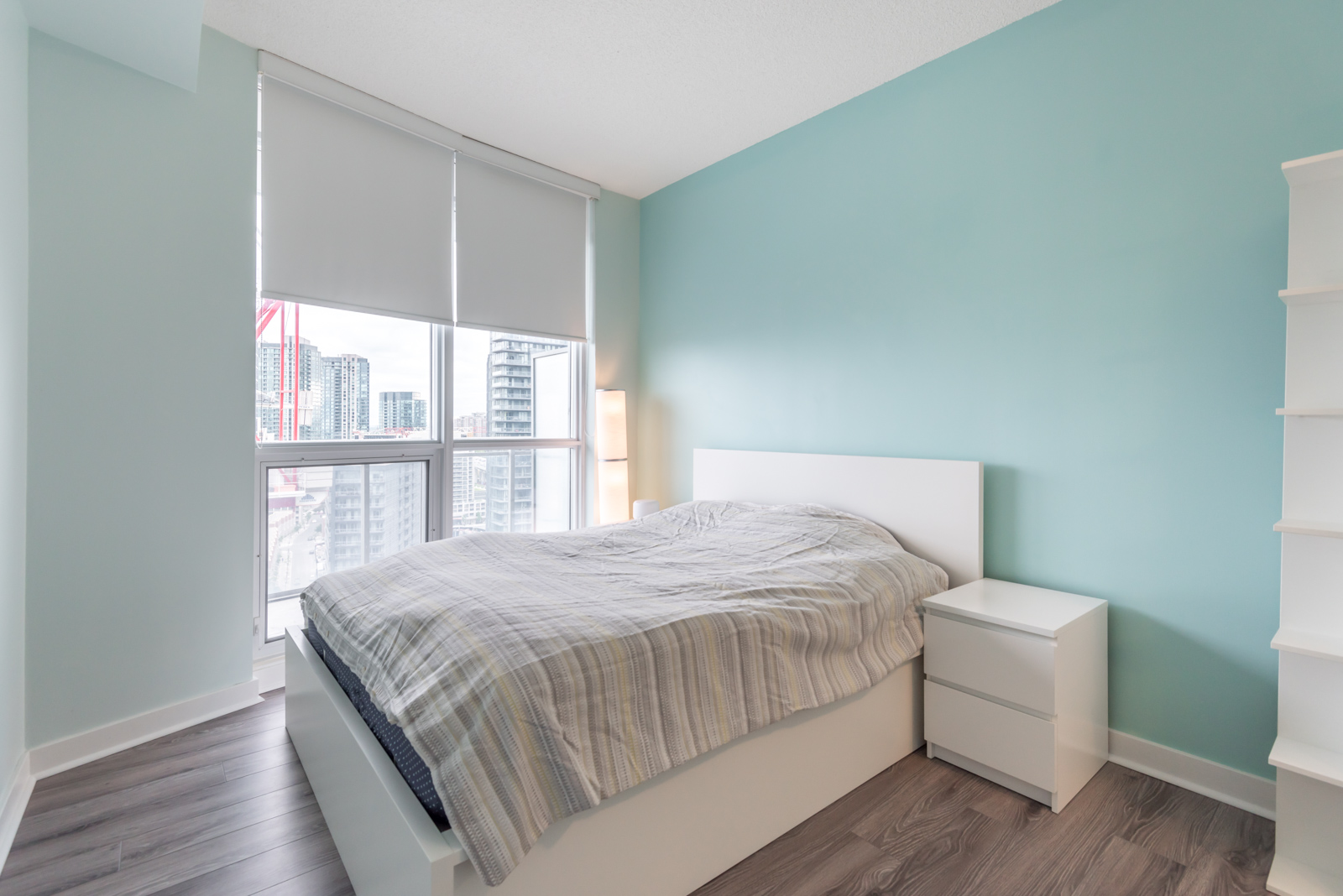 A photo of the master bedroom. We also see the windows and city behind them, and blue walls.