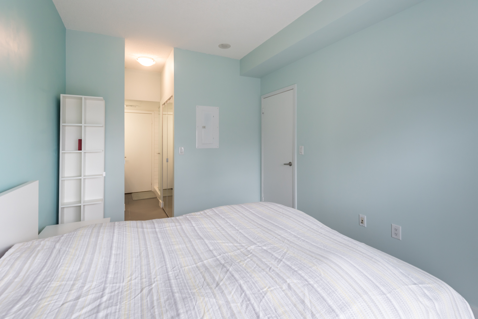 Another side of the bedroom. We see the closet and also the bathroom door.