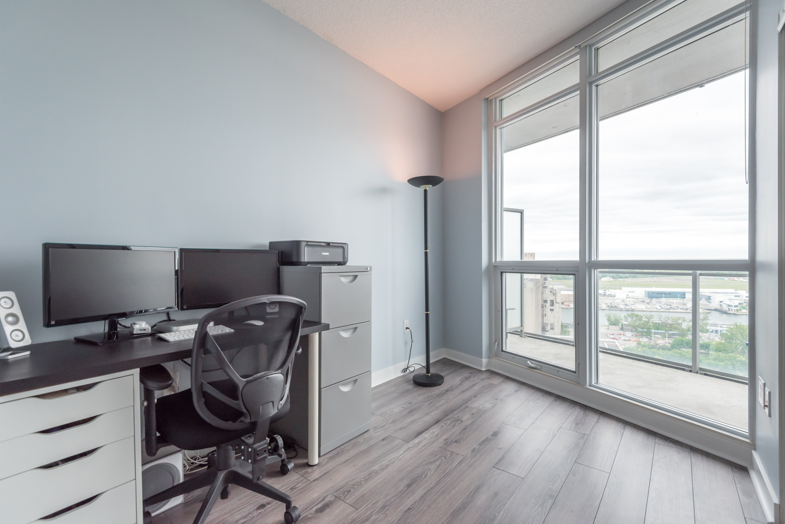 Image of second bedroom and another view of balcony. It also shows a desk and chair and laminate floors.