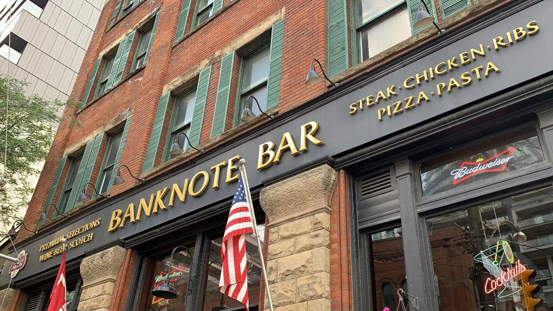 Black and gold sign for Banknote Bar with American flag on King St West Toronto.