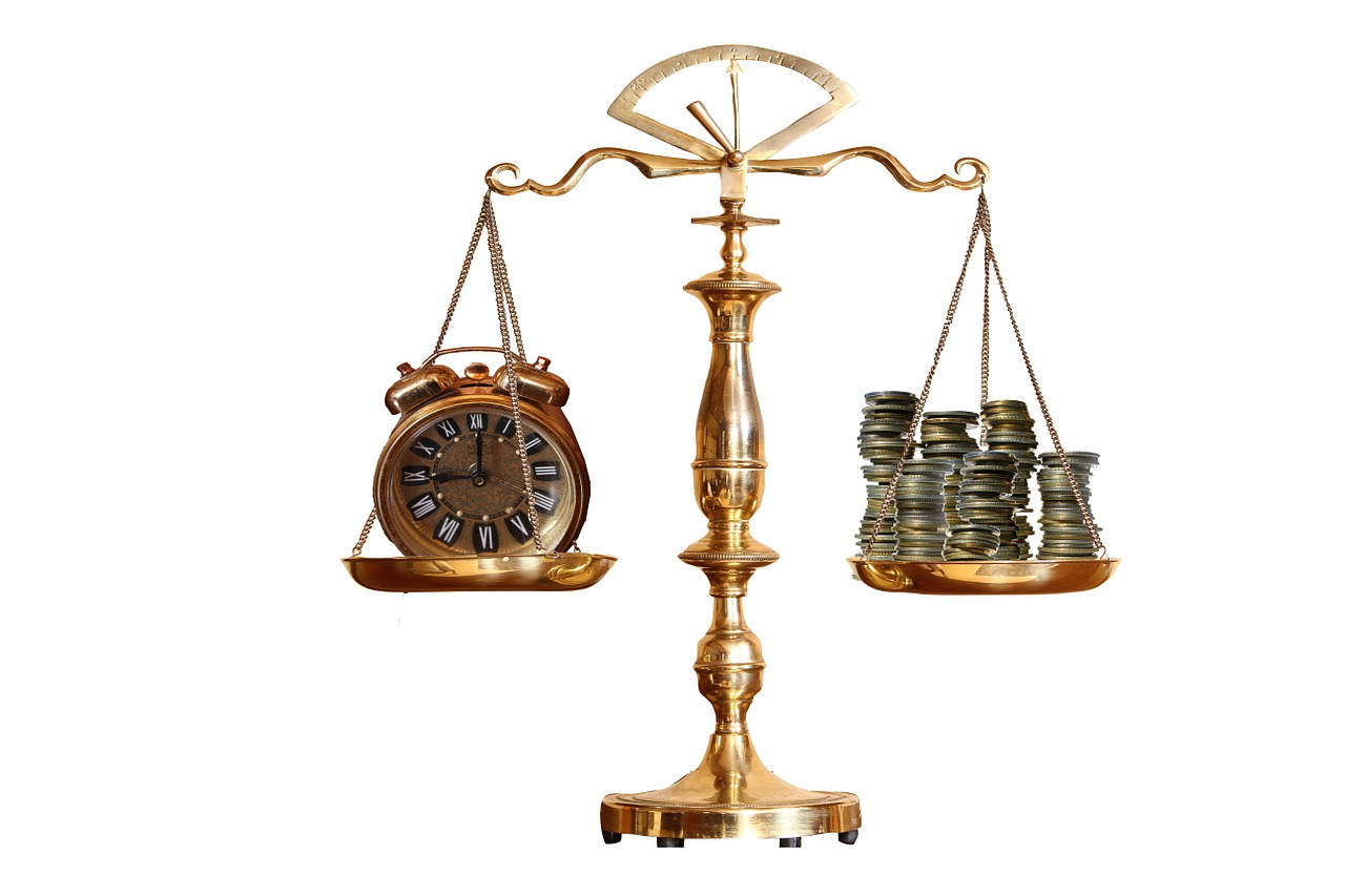 Pic of scales showing clock and money.