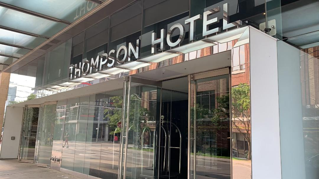 Entrance of the Thompson Hotel Toronto with silver letters.