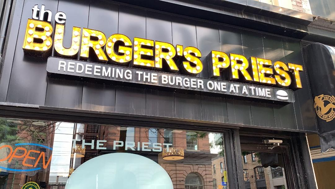 Bright yellow sign for The Burger's Priest on King St W Toronto.