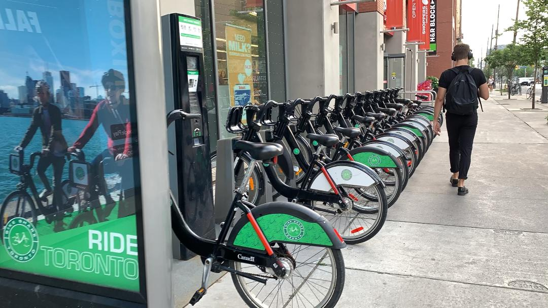 Several black and green bicycles in a row at Bike Share ride program.