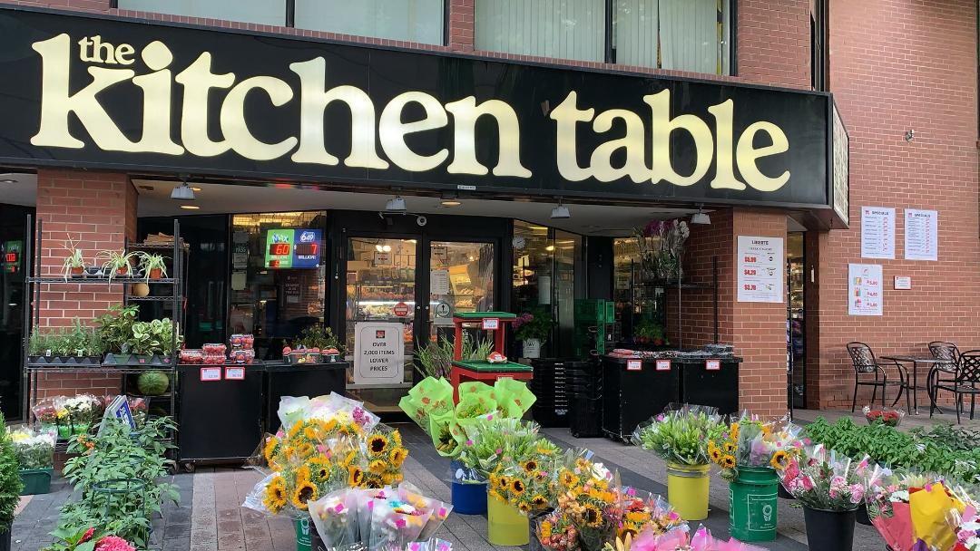 Colourful flowers and flowerpots outside The Kitchen Table grocery store with huge lettering.