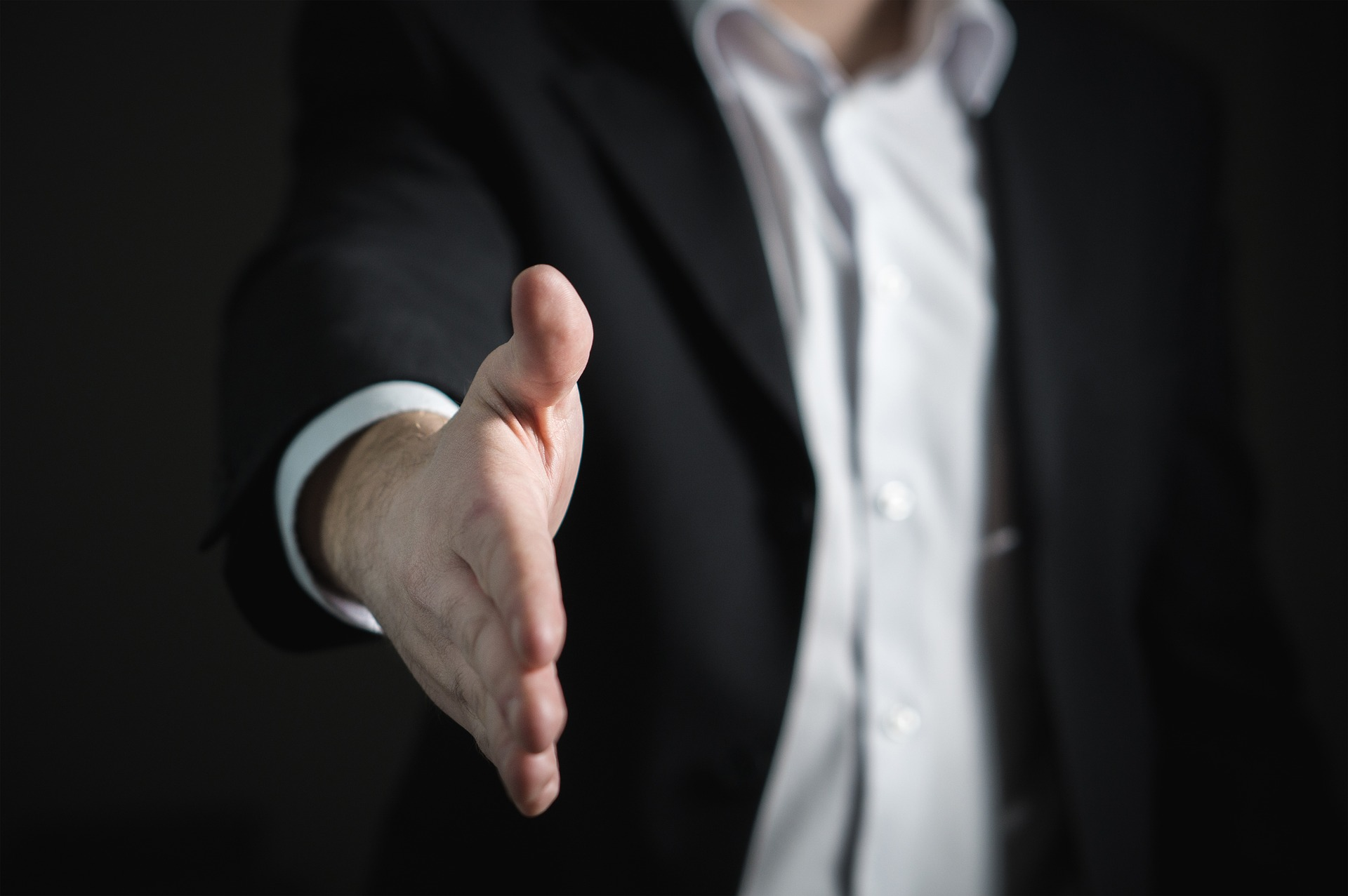 Man reaching out to shake hand. He is wearing a suit to show how hiring a realtor needs to dress the part.