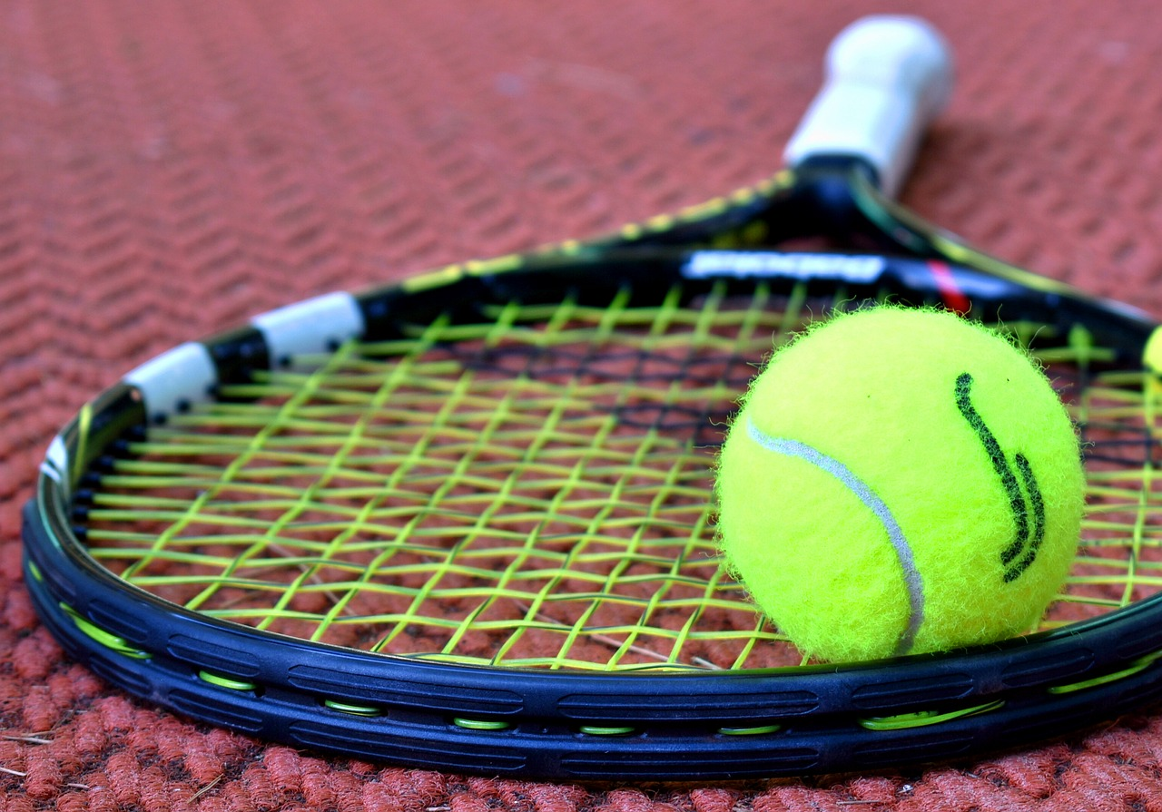 Another close up image, this one shows a tennis ball and racket and a purple background.