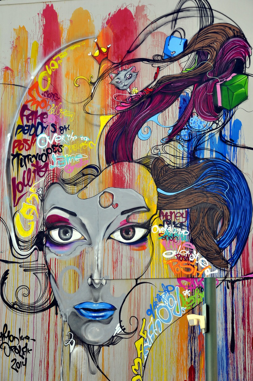 A colorful mural of a lady and we also see cats and hair and words. The Riverdale Art Walk is also famous for murals.