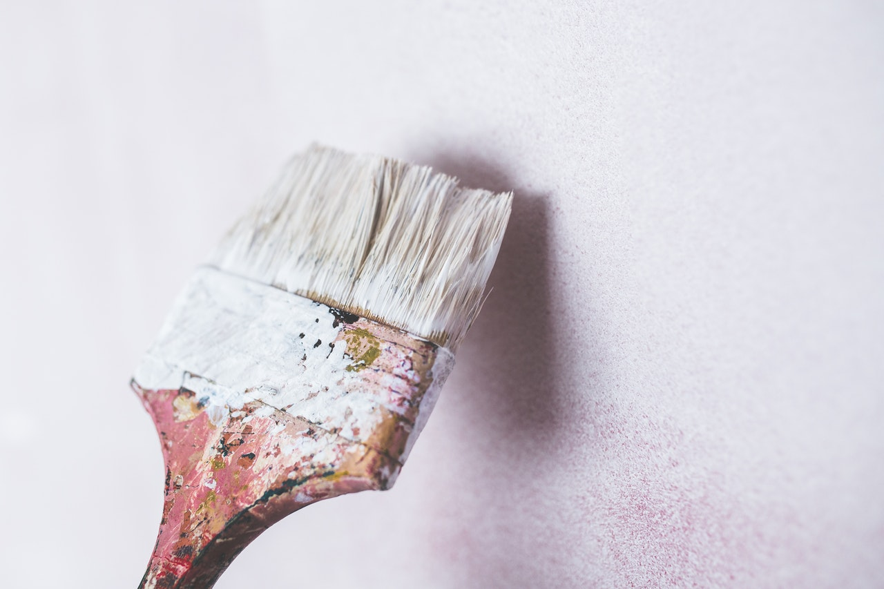 Image of a paint brush covered in white paint and a wall.