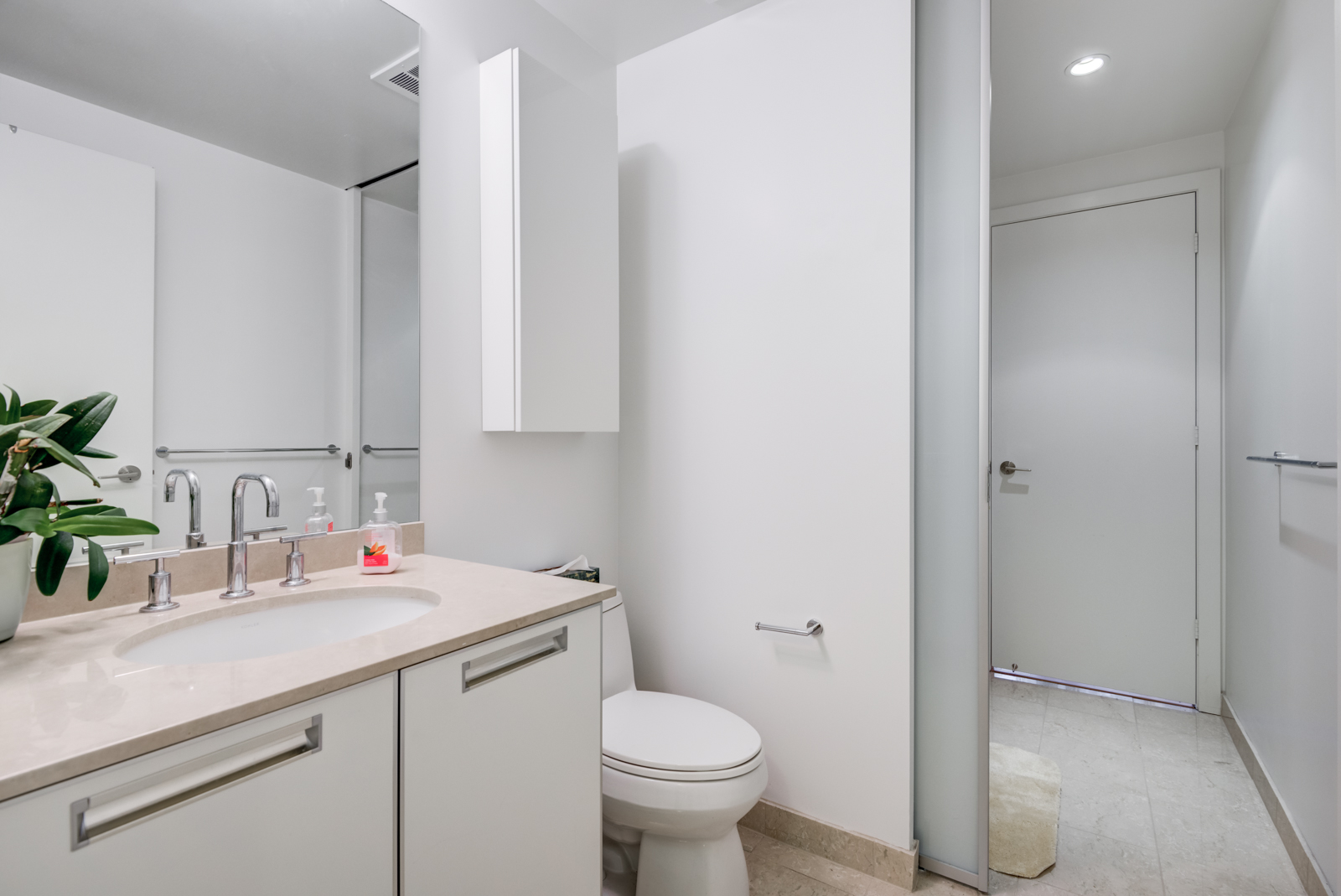 Our first look at 33 Charles St E Unit 911 bathroom. We see the sink, mirror and toilet.