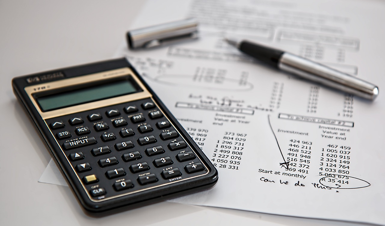 Calculator, pen and paper showing money required for custom home