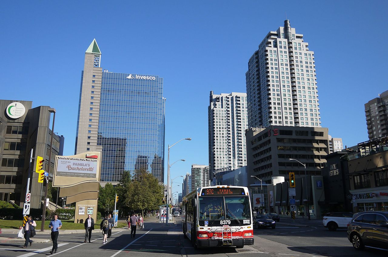 Photo of Downtown North York and bus and people and buildings and streets.