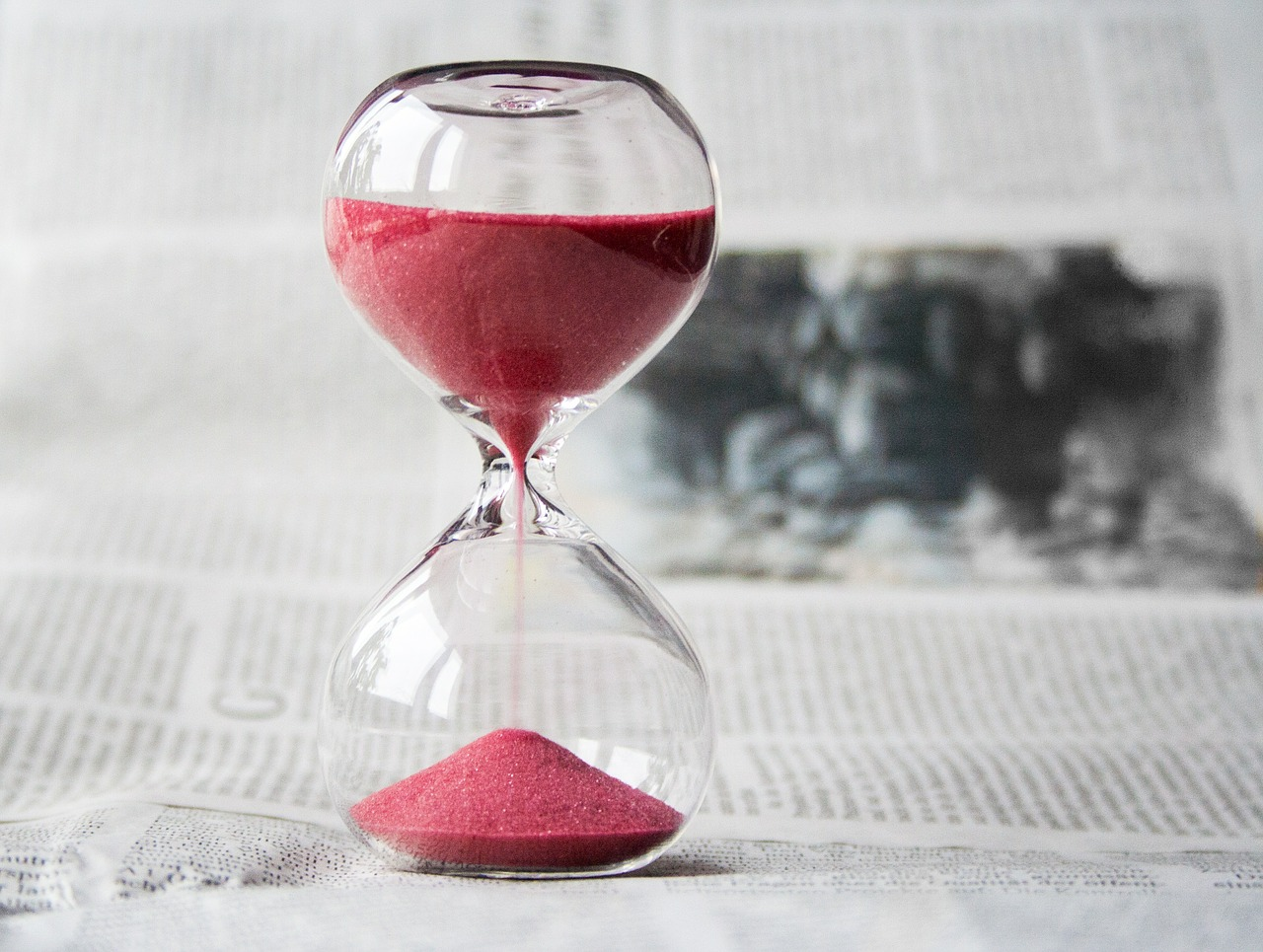 Hourglass with red sand; shows links between time and money.