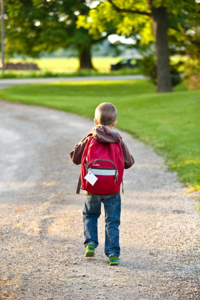 Kid with backpack walking to school