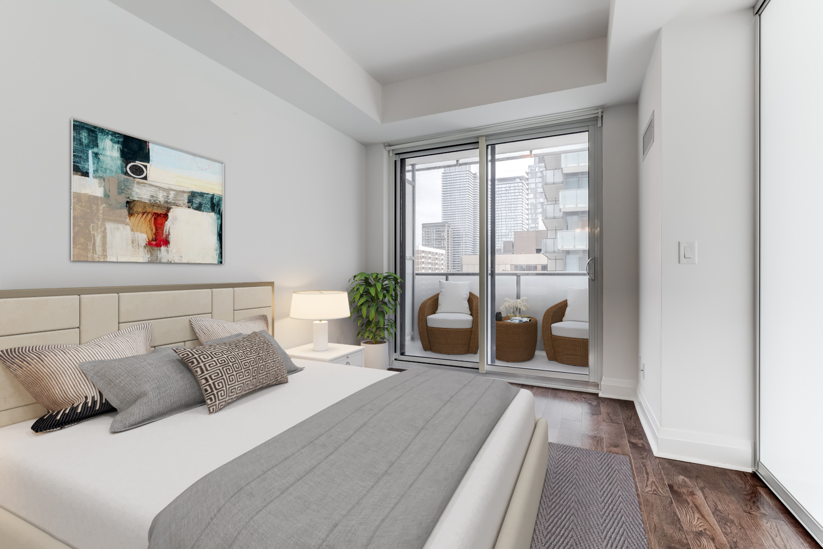 Unit 1502 master bedroom, virtually staged with bed and pillows and art.