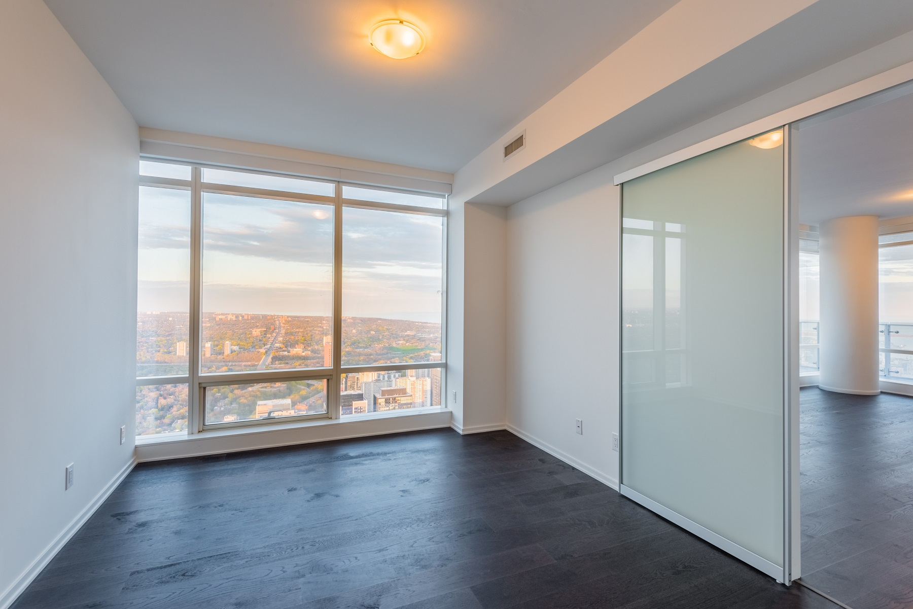 The master bedroom is tall, spacious and offers scenic views of Toronto.