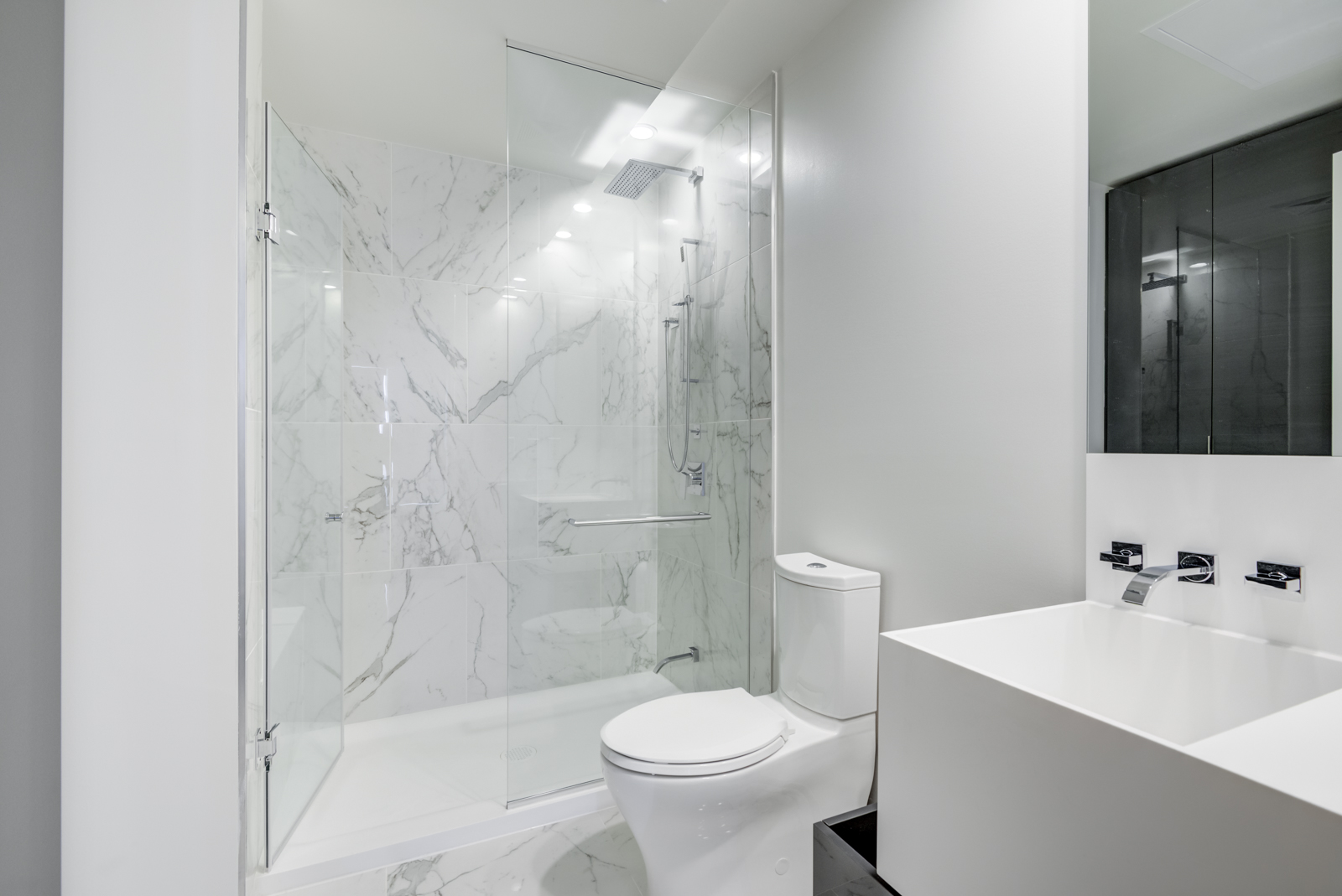 Highlights include a large sink, wall-mounted faucet, tall mirror, and frameless walk-in shower.