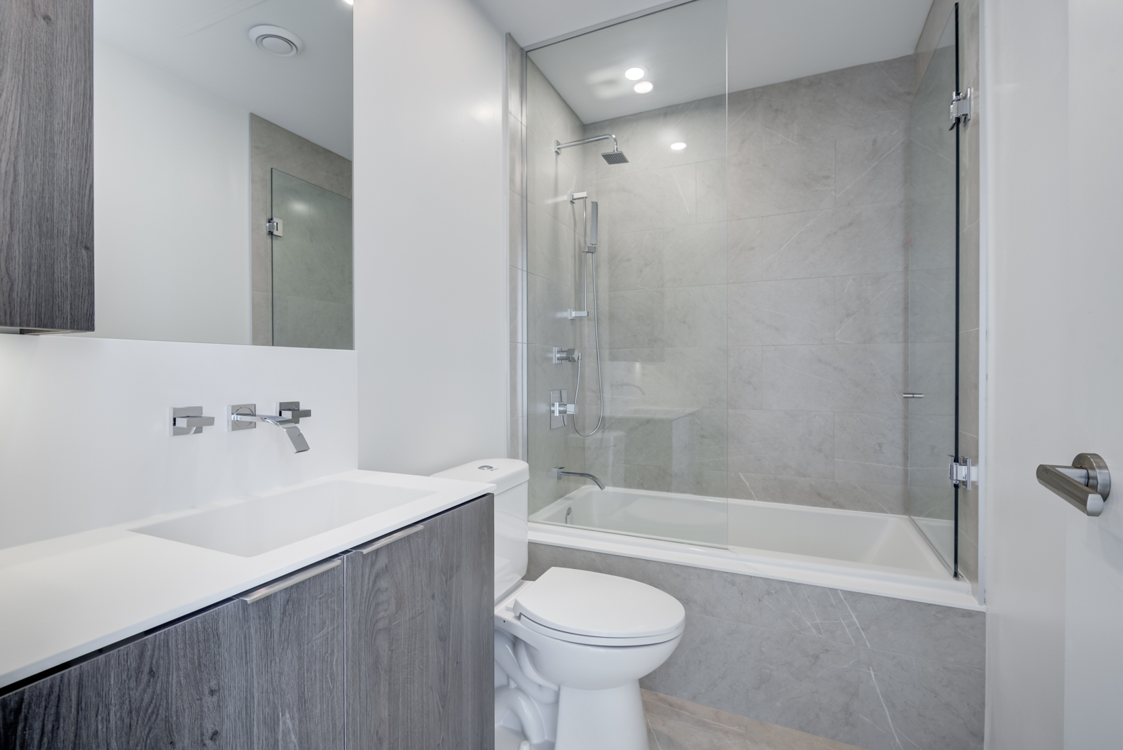 Photo of bathroom and sink, faucet, tub and shower.