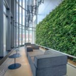Lobby of Monde Condos; we can see chairs and tables and a wall of green.