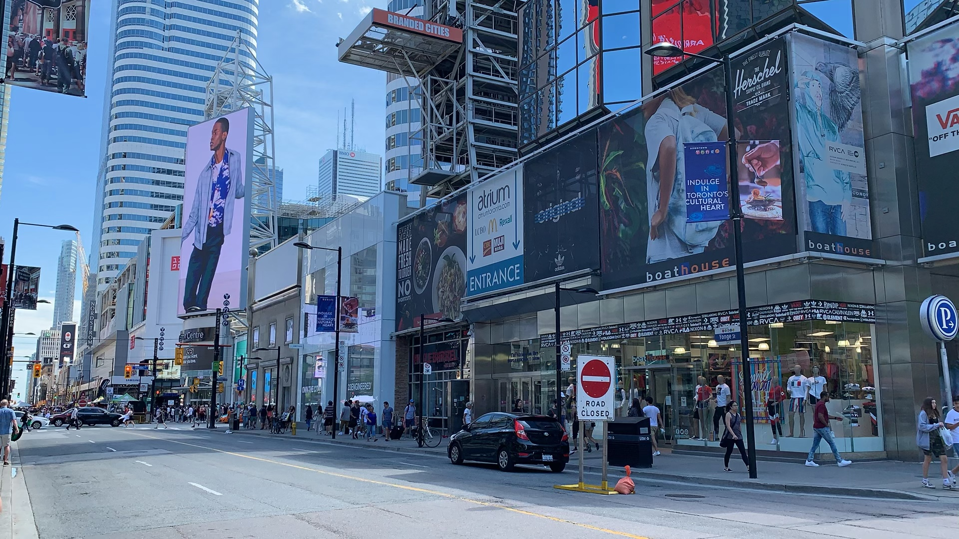 Photo of Yonge and Dundas in Toronto with large billboards people walking on street.
