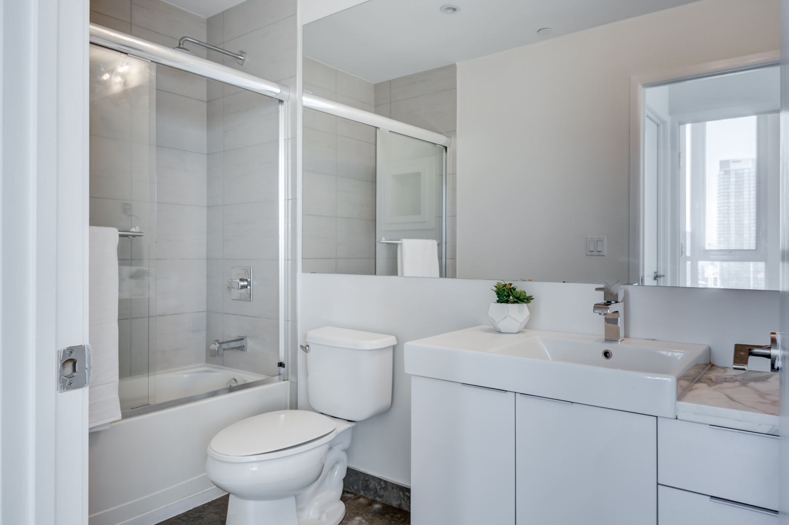 Second bathroom with tub and porcelain tiles at Victory Lofts Penthouse Suite in 478 King St W Toronto.