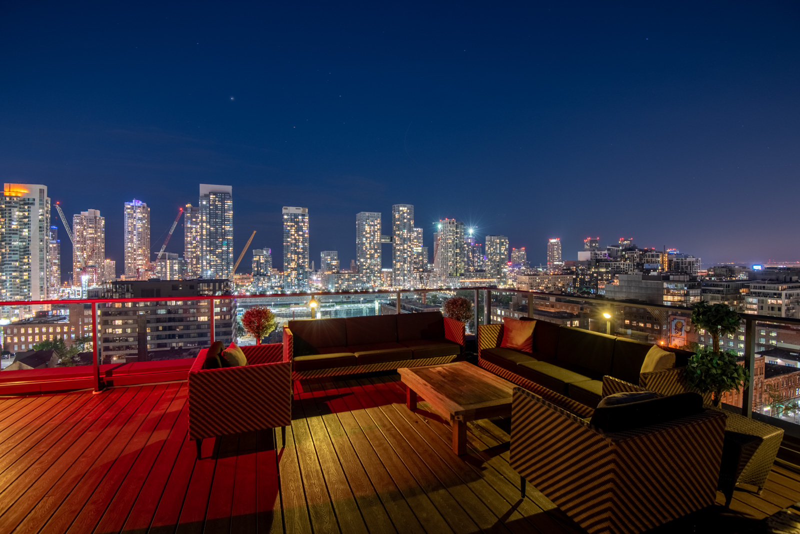 Night view of terrace and deck and Toronto from Victory Lofts Penthouse Suite in 478 King St W Toronto.