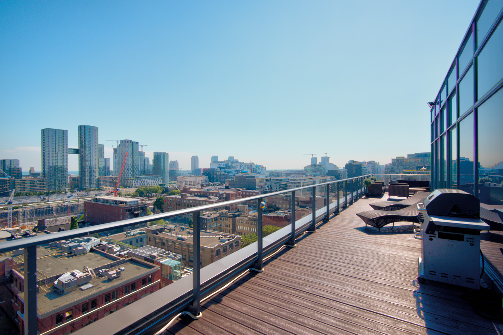 BBQ and lounge chairs with view of Toronto from terrace of Victory Lofts Penthouse Suite in 478 King St W Toronto.