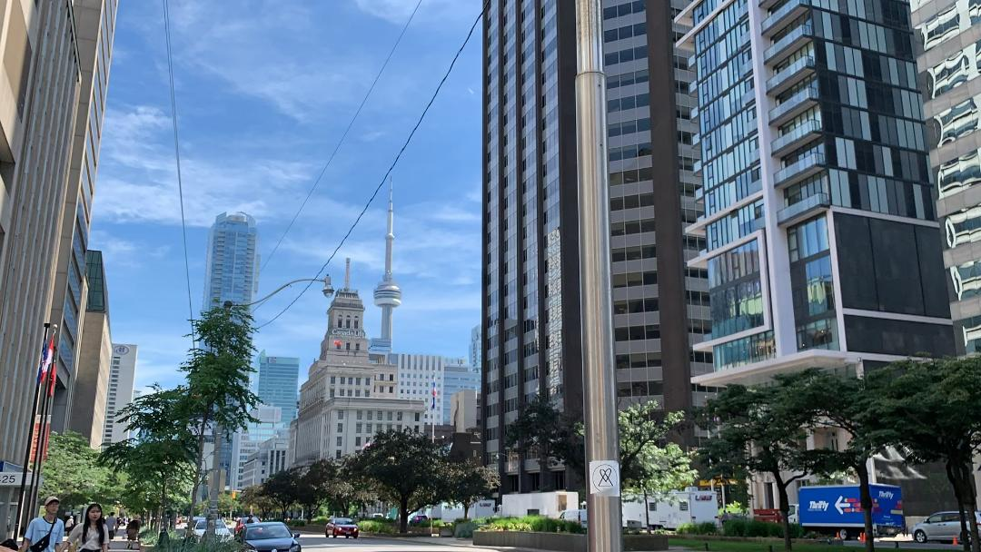 Street view of condos, people, Canada Life Building and CN Tower from Yonge and Dundas.