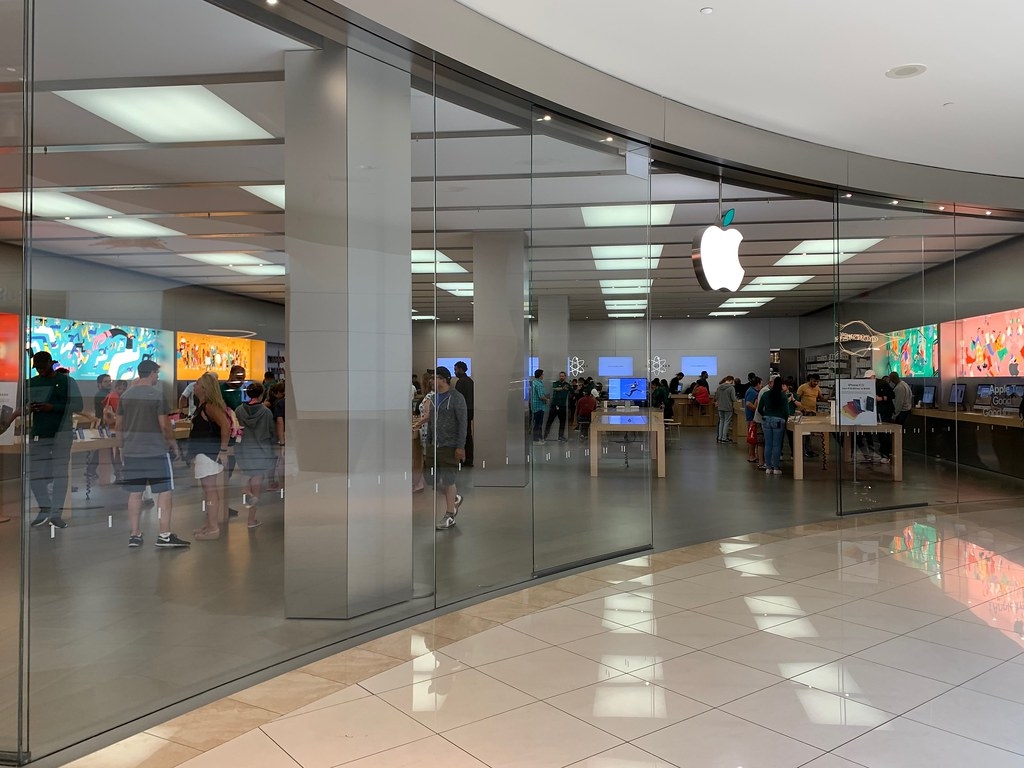 Apple storefront with glass displays and customers.