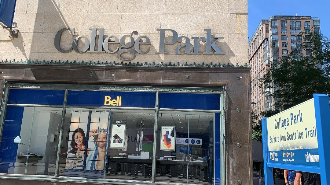 Dark gray sign for College Park mall in Toronto above store.