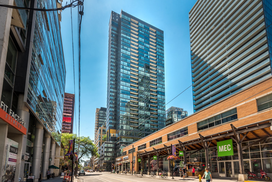 Daytime view of Charlie Condos from street surrounded by shops and condos.