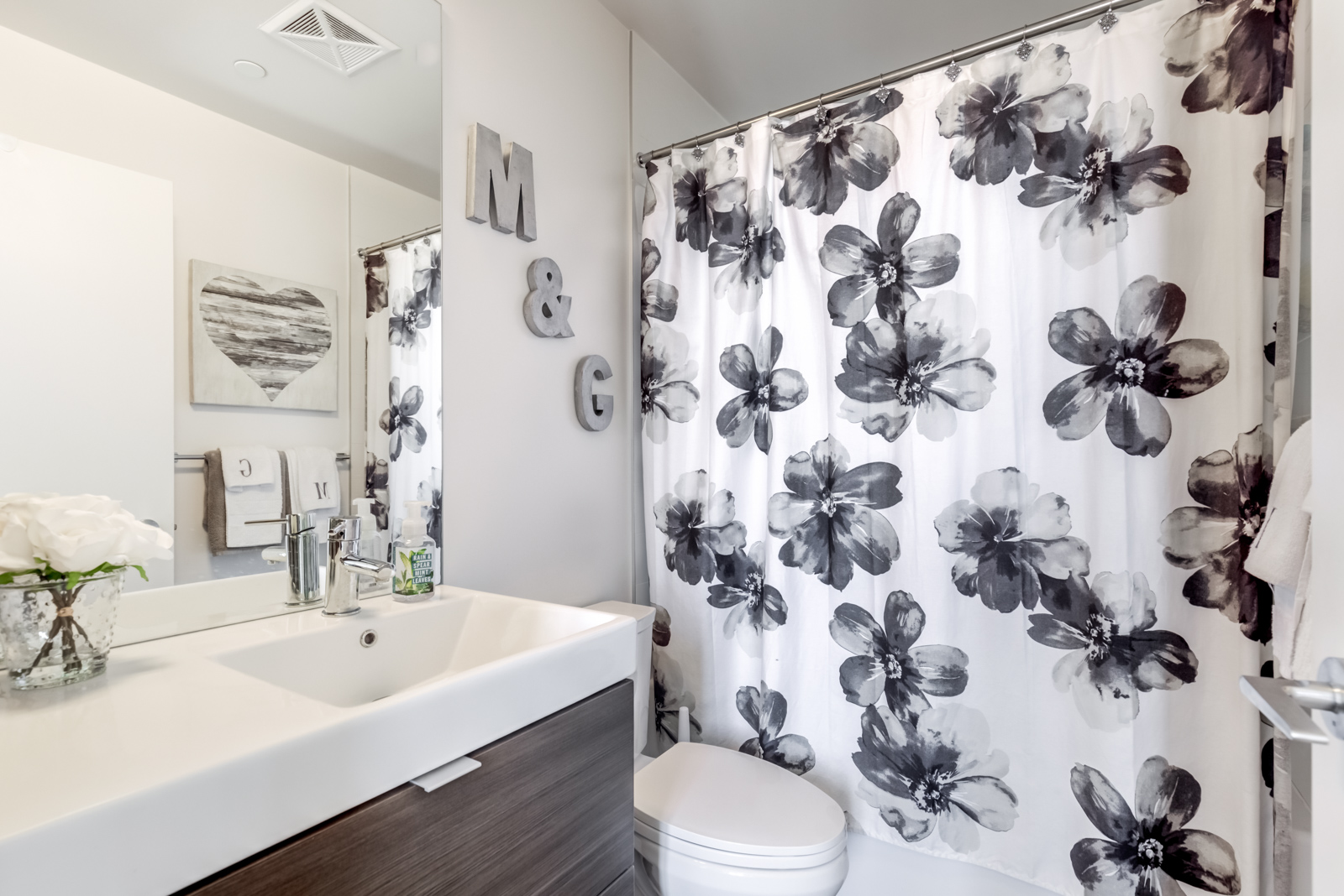Master bathroom with vanity, white sink wooden cabinets, and floral bathtub curtain.