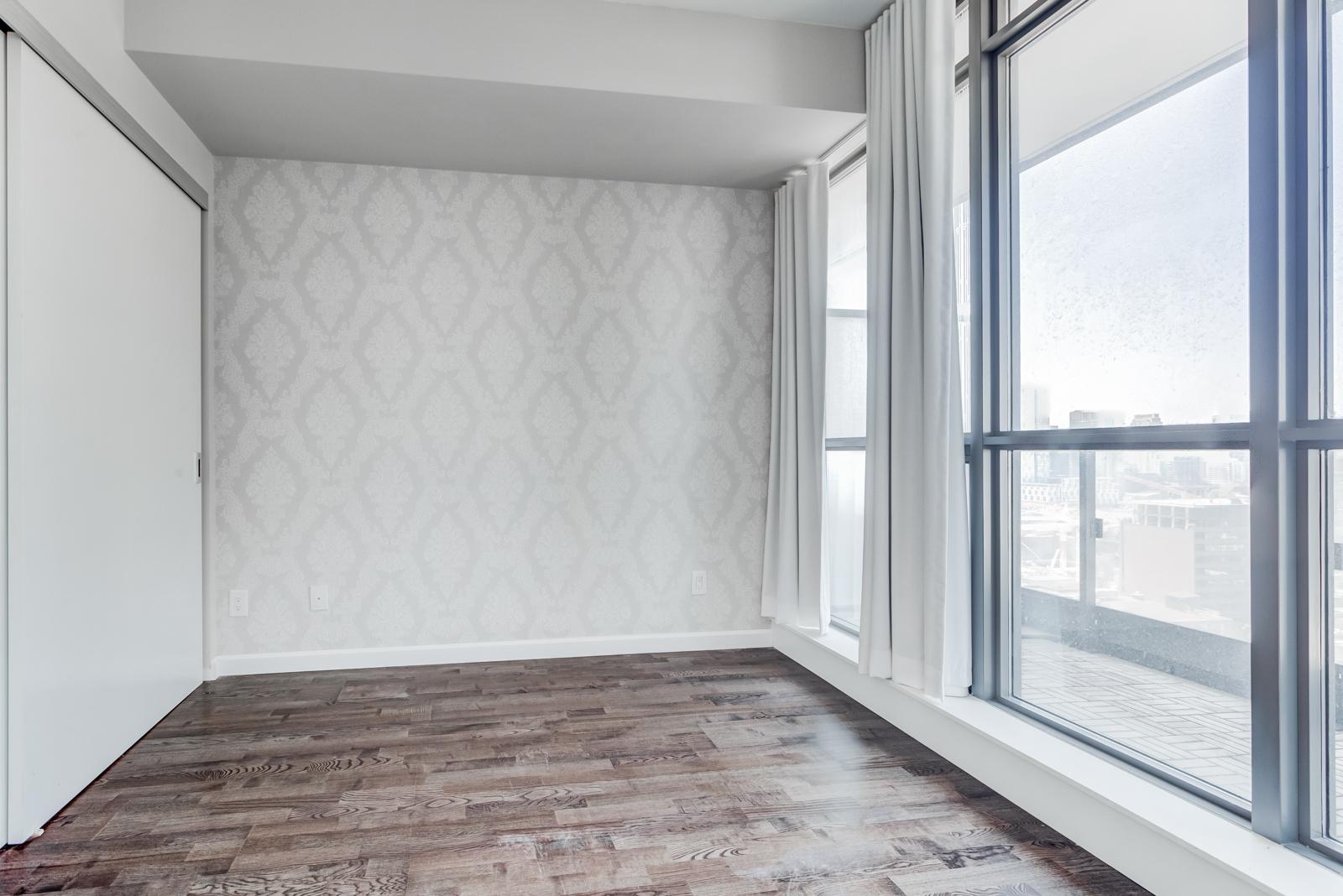 Empty master bedroom with huge windows, dark laminate floors and gray walls.