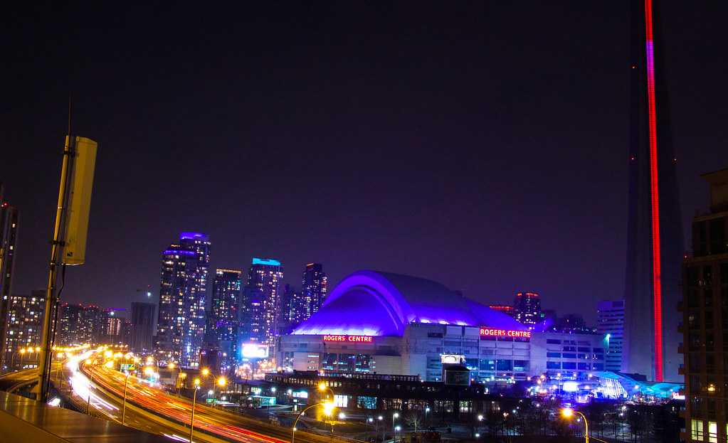 Toronto's Rogers Centre at night with blue dome and red lettering.