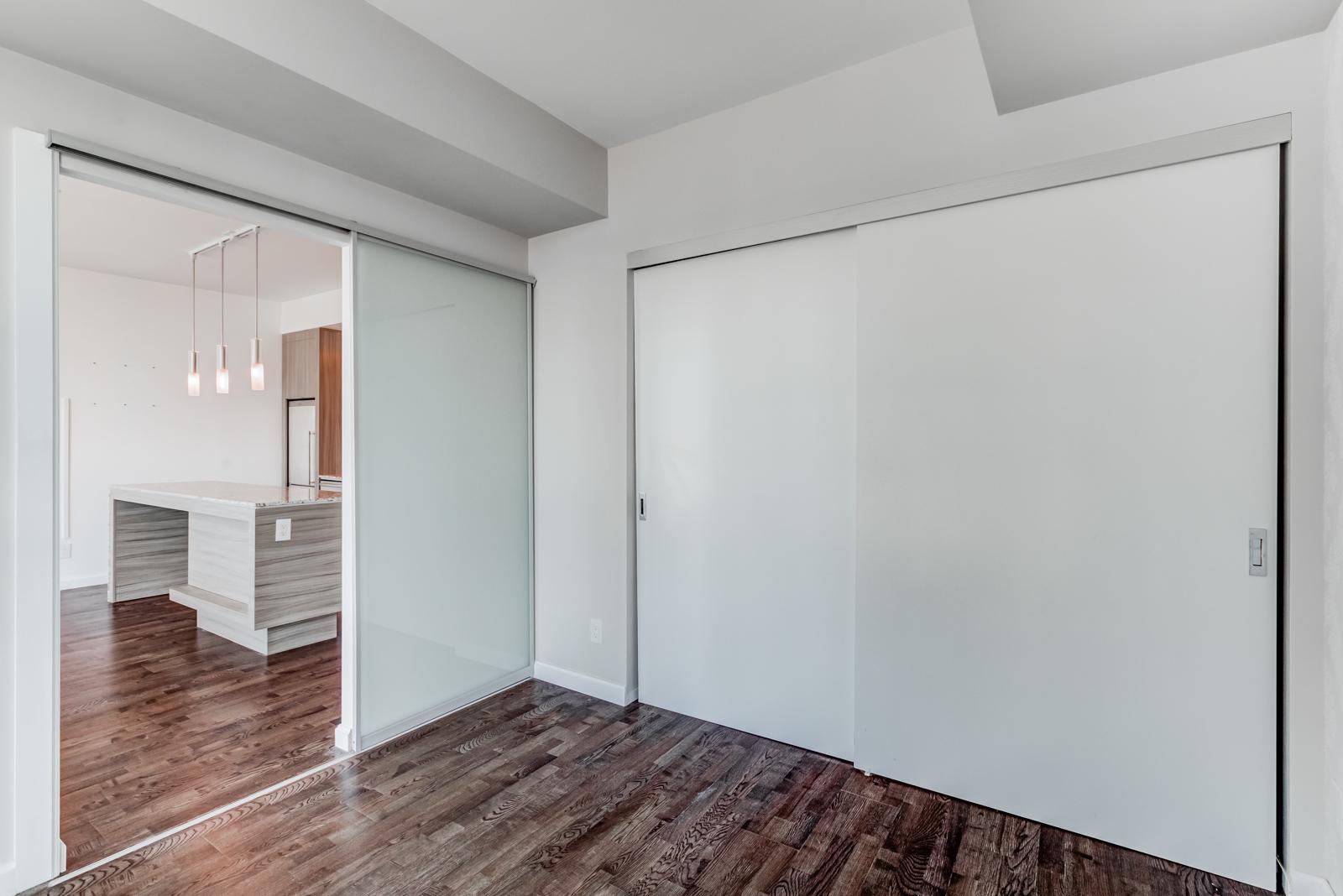 Master bedroom closet with dual gray sliding doors.
